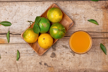 Fresh peeled tangerine juice in glass on wooden background.