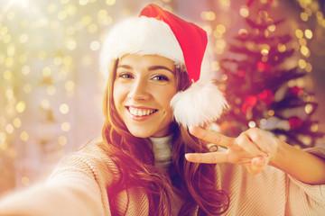 happy woman taking selfie over christmas tree