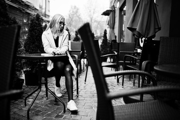 Blonde girl at glasses and pink coat, black tunic sitting at table outdoor cafe.