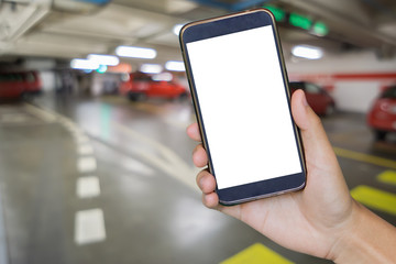 Man hand holding mobile smart phone,tablet,cellphone over Blur of backgrond with  parking area with perspective view,blur image with bokeh of Car park interior for background usage.vintage photo