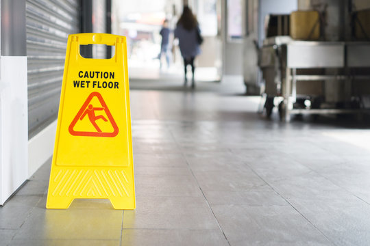 yellow sign inside building hallway showing warning of caution wet floor,selective focus,vintage color.