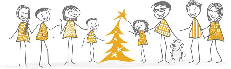 Un enfant décore le sapin de Noël aidé de sa famille et d'amis
