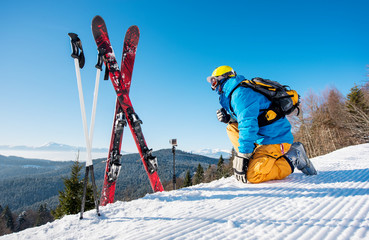 Rearview shot of a skier enjoying on top of the mountain beautiful snowy mountains view near his skiing equipment relaxing people enjoyment recreation travelling riding