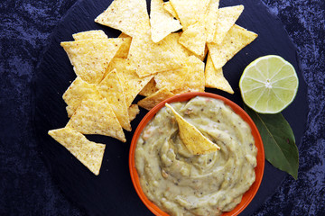 Bowl of guacamole with tortilla chips on dark background.