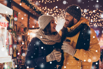 Having fun together at a christmas fairy with snowfall. Young cheerful couple is having a walk with hot drinks, enjoying, dressed warm, looking at each other and laugh, snowflakes all around