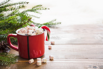 Red cup of hot chocolate with marshmallow on windowsill. Weekend concept. Home style. Christmas time.