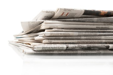 Pile of newspapers on white background, close up