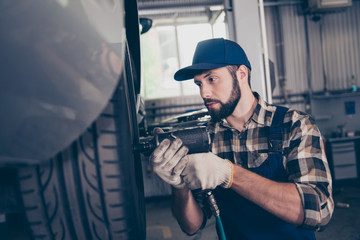 Serious brunet bearded brunet engineer handyman in checkered shirt, hat head wear is torquing lugs nuts of wheel at a garage station, ceiling background. Technology, safety concept