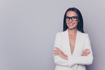 Close up portrait of caucasian gorgeous stunning charming lovely cute expert business lady, standing on pure light grey background, grinning, in black cool specs, with crossed arms