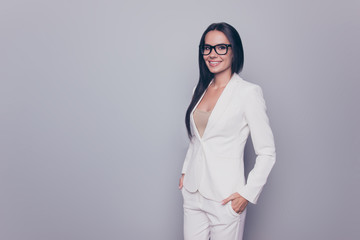 Cute gorgeous well dressed by formal dress code stunning charming expert business lady, standing on pure light background, grinning, in black cool specs, with arms in pants