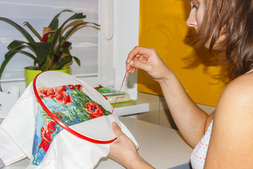 girl is embroidering picture with colorful threads. hobby at home. Make your own hands. picture of Handmade.