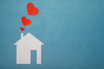 Concept of love in house. White paper house on blue textured background with red hearts from pipe. Smoke from pipe in form of paper red hearts. LOVE, family, home.