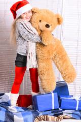 Santas helper in red hat holds huge toy bear