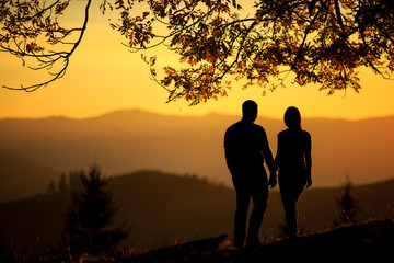 Young couple hiking outdoors with backpacks during sunset. Silhouette of a couple on the top of a rock mountain view of sunset.  activeactivityadventurealtitudeautumnbackpackbackpackingcampingcliffcli