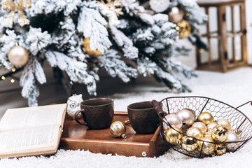 Close-up photo of a tray with two cups of hot drinks and a book. Christmas and New Year concept