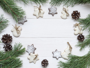 Christmas frame, background for greeting card. Decoration, fir tree, choco and sugar-glaze cookies on white wooden table. Top view, copy space.