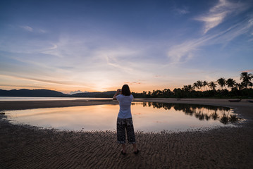 Woman traveler taking a sunset photo on the beach in Thailand.