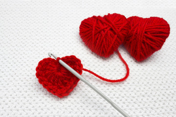 A handmade crocheted wool organic red heart. Old metal crocheting hook and two red yarn ball like a heart on the white crochet background. Red heart made of wool yarn and crochet heart. Soft focus.