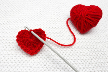Old metal crocheting hook and red yarn ball like a heart on the white crochet background. A handmade crocheted wool organic red heart. Red heart made of wool yarn and crochet heart. Soft focus.
