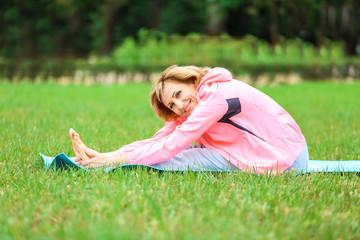 Elderly woman doing yoga in park