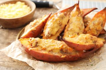 Plate with yummy stuffed sweet potato on kitchen table
