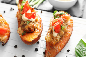 Yummy stuffed sweet potato on wooden board