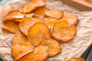 Yummy sweet potato chips on table