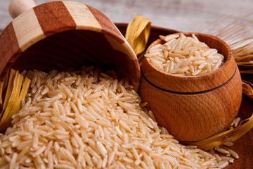 A close-up image of rice is poured from a small wooden bowl.