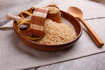 Composition with raw rice in a brown bowl with a wooden spatula and a spoon.