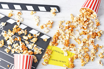 Caramel popcorn, tickets and movie clapper on white wooden background