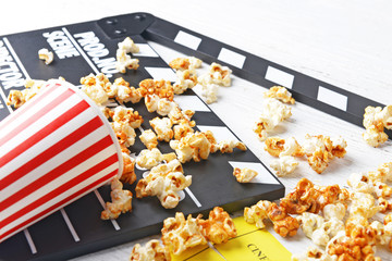 Caramel popcorn and movie clapper on white wooden background