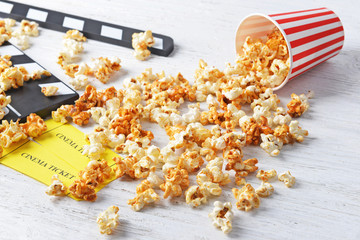 Caramel popcorn, tickets and movie clapper on wooden background