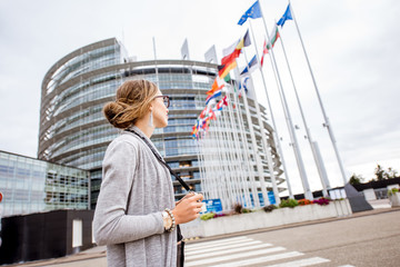 Young woman tourist standing with photo camera in front of the European parliament building in Strasbourg, France