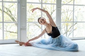 Ballerina in a blue ballet tutu skirt. Beautiful graceful ballerine practice ballet positions near large window in white light hall. Young classical Ballet dancer side view. Ballet class training
