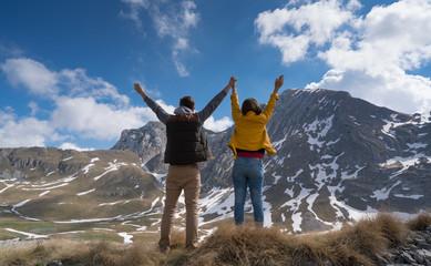 Happy joyful young couple walking on the foothills together.