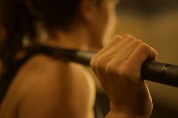 Close-up on the hand of a female weight lifter with a barbell on her back