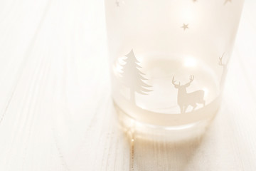 merry christmas. lantern with deers and tree with illumination lights on white wooden background with space for text. seasonal greetings card. happy holidays. xmas