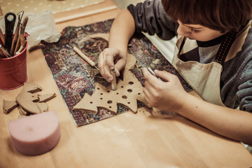 The child is engaged in a pottery school, sculpts a clay product