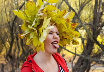 The girl shows her tongue. Girl in a red jacket with a wreath of yellow autumn leaves. The Queen of Autumn. Miss autumn. Autumn Walk.