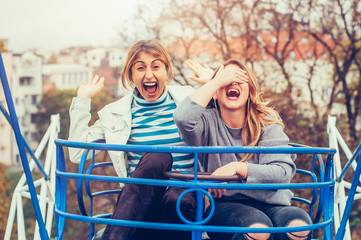 Two cheerful girls having fun on merry go round