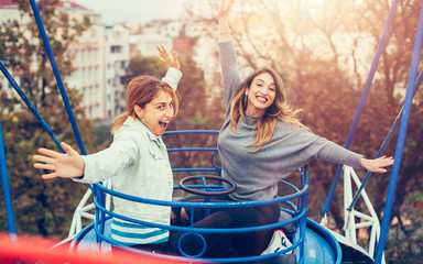 Two cheerful girls having fun on merry go round