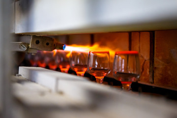 Glass blowing process, Manufacture of glassware, Someone is manufacturing glass products.