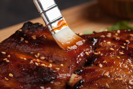Close-up chef spreading sauce bbq on ribs with brush