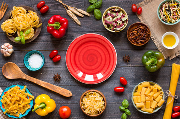 Different types of pasta with various types of vegetables, health or vegetarian concept on a wooden background,  Top view