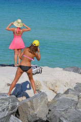 Woman in pink sundress wearing a straw hat posing while her daughter  snaps a smart phone photo at Southpointe Park in Mimi Beach,Florida