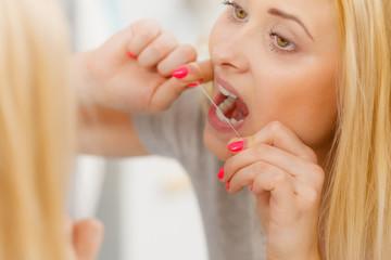 Woman cleaning her teeth using dental floss