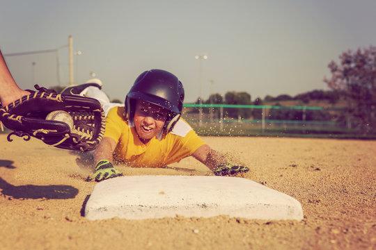 Youth Baseball playing sliding back to base.