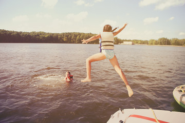 Kids jumping off a boat into the lake. Vintage film effect, noise and color fringing, dark edges