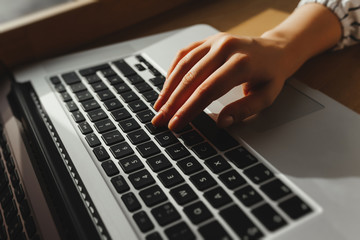 Working at cafe with laptop woman writing a blog. Female hands on the keyboard