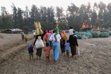 A group of Rohingya refugees, who fled last night from Myanmar by boat, walks towards a makeshift camp in Cox's Bazar